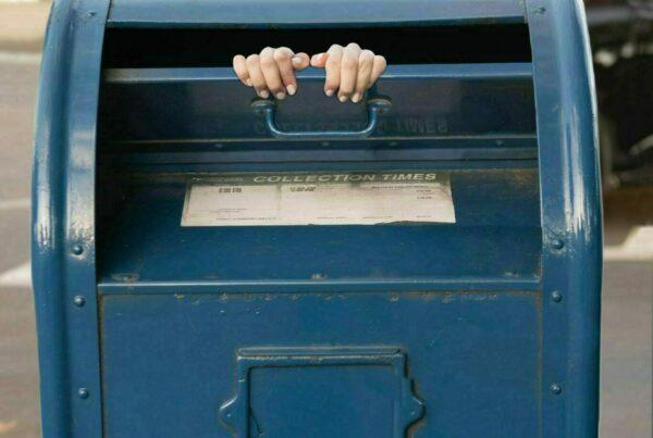 person inside blue steel mailbox